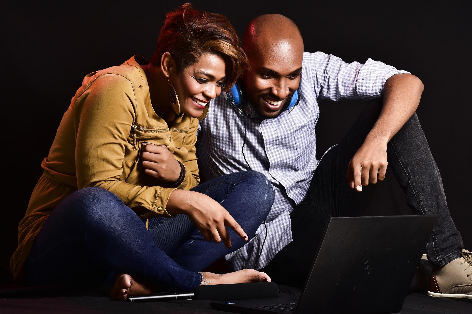 mężczyzna i kobieta oglądający coś na komputerze