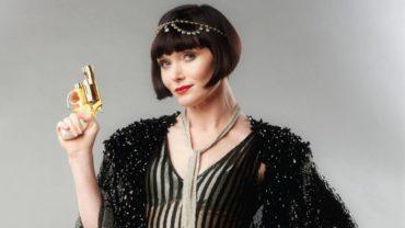 Zagadki kryminalne panny Fisher baner. Arystokrata z lat 20. XX wieku trzymająca w ręku złoty pistolet.